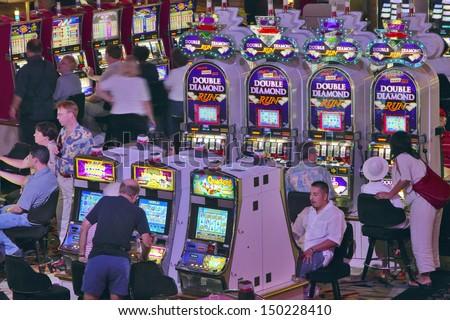 LAS VEGAS, NEVADA - CIRCA 2004: Rows of slot machines and gamblers at Rio Casino in Las Vegas, NV - stock photo