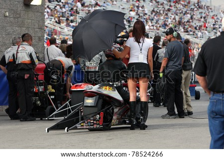 LAS VEGAS NEVADA - MAY 12: unidentified female, holding an umbrella for shade over a bike drag racer, a few minutes before start to the NHRA drag racing finals on May 12, 2008 in Las Vegas Nevada. - stock photo