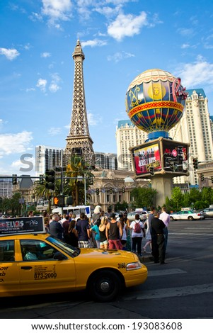 LAS VEGAS,NEVADA,USA-AUGUST 2,2012: tourists crossing the famous strip of las vegas to go and see the various hotels and casino.in this pictures there is Ballys tower - stock photo