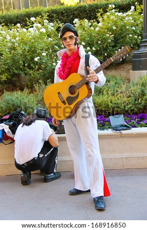 LAS VEGAS, NEVADA, USA - OCTOBER 20, 2013  : Actor dressed as Elvis Presley poses for the camera in Las Vegas, Nevada. Many actors in different costumes entertain tourists in Las Vegas - stock photo