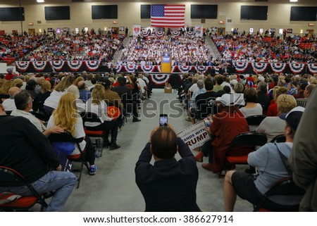 LAS VEGAS, NV - FEBRUARY 22: Supporters cheer underneath US Flag as they wait for Republican presidential candidate Donald Trump to speak at a rally at the South Point Las Vegas, NV - taking picture. - stock photo