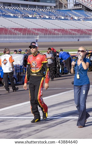 LAS VEGAS, NV - SEPTEMBER 26, 2009: Aric Almirola walks through the pit area with his girlfriend Janice Goss before the Sept. 26, 2009 Las Vegas 350 truck race. - stock photo