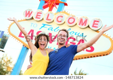 Las vegas people - couple happy cheering by sign. Welcome to Las Vegas sign billboard and excited cheerful young multiracial couple having fun on the strip during travel holiday vacation, Nevada, USA. - stock photo