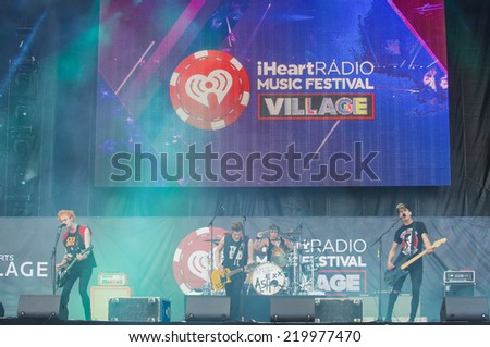 LAS VEGAS - SEP 20: Musician Michael Clifford of 5 Seconds of Summer performs on stage at the 2014 iHeartRadio Music Festival Village on September 20, 2014 in Las Vegas. - stock photo