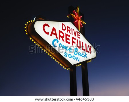 Las Vegas sign at night reading Drive carefully and Come back soon. Horizontally framed shot. - stock photo