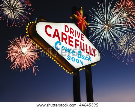 Las Vegas sign at night reading Drive carefully and Come back soon with fireworks in background. Horizontally framed shot. - stock photo