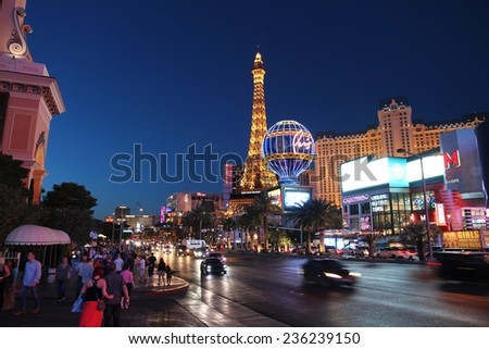 LAS VEGAS, USA - APRIL 14, 2014: People visit the famous Strip in Las Vegas. 15 of 25 largest hotels in the world are located at the strip with more than 60 thousand rooms. - stock photo