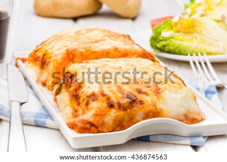 lasagna baked in porcelain tray on wooden table