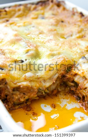 Lasagna bolognese in a square white ceramic tray - close up