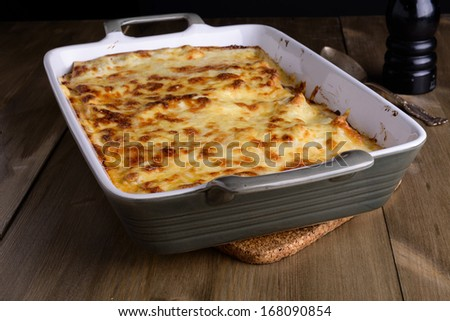 Lasagna in a serving plate with cheese on top on an old wood table - stock photo