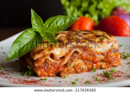 Lasagna on a square white plate with Italian basil - stock photo
