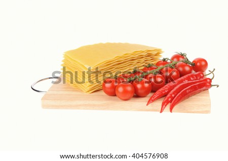 Lasagna pasta and tomato and red peppers on cutting board isolated on white background - stock photo