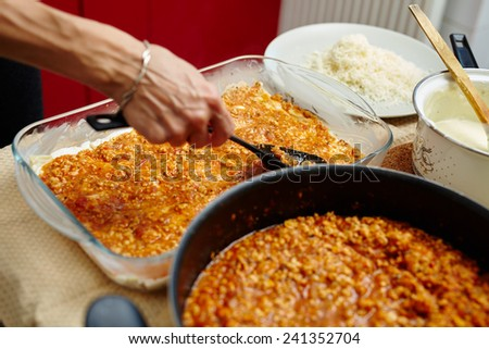 Lasagna preparation with filling in a frying pan and tray, grated parmesan and bechamel sauce - stock photo