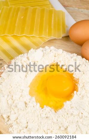 Lasagna sheets next to ingredients to prepare dough - stock photo