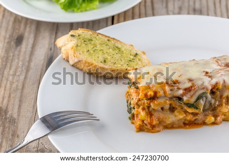 Lasagna with garlic bread on a wooden table - stock photo