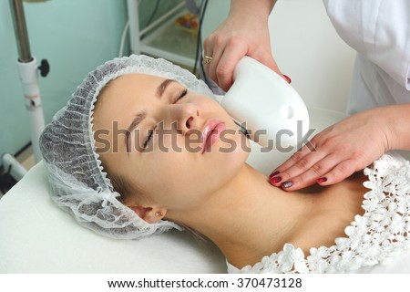 Laser hair removal in the beauty salon. Woman having facial hair removal. Laser hair removal equipment in the background.
