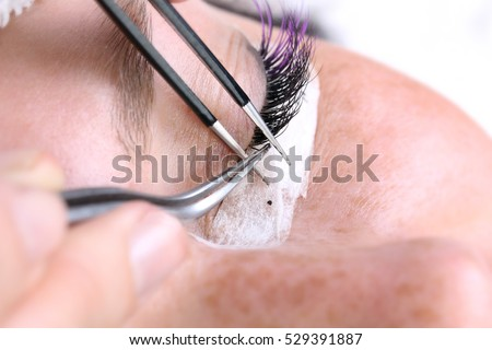 Lash making process, extreme long lashes and tweezers, woman eyelash extension