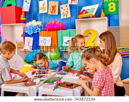Lasrge Group beauty kids sculpt by plasticine on table in kindergarten . - stock photo