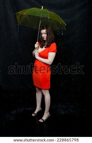 lass wearing red dress stands under an umbrella - stock photo
