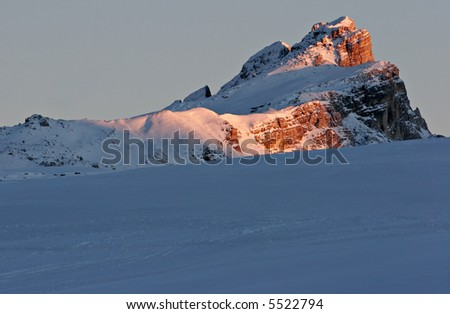 Last afternoon sun hitting Dolomite mountain on ski slope - stock photo