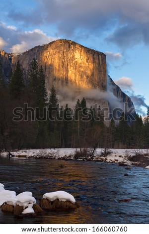 Last light kisses the face of El Capitan in Yosemite National Park as seen from the Merced River. - stock photo