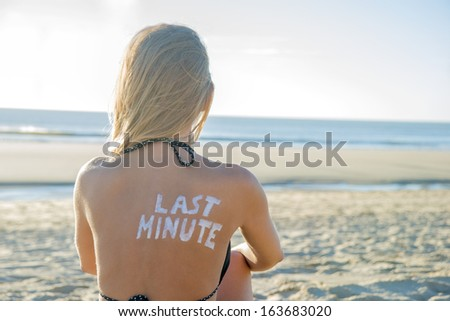 Last Minute written with sunscreen on back of attractive woman sitting on beach looking at ocean - stock photo