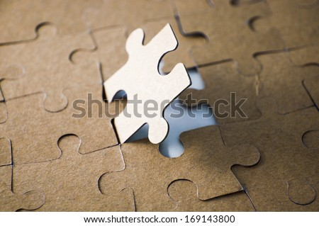 Last piece of jigsaw puzzle - golden tone - stock photo
