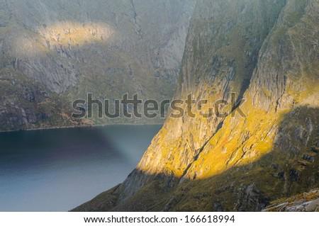 Last rays of sunlight falling on spectacular steep mountain ridge, Lofoten islands, Norway - stock photo