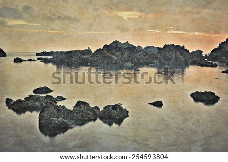 last rays of sunlight over the shoreline - Textured effect - stock photo