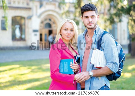 Last school days. Couple of students standing together holding books looking at the camera while standing on the grass against the building of the university - stock photo