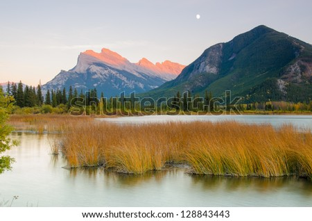 Last sunlight falling on mountains by a lake