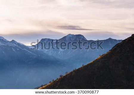 Last sunlight hitting a steep ridge in the foreground with scenic cloudscape and moody sky over majestic snocapped mountain range in the background. Mist in the valley below, Italian French Alps.