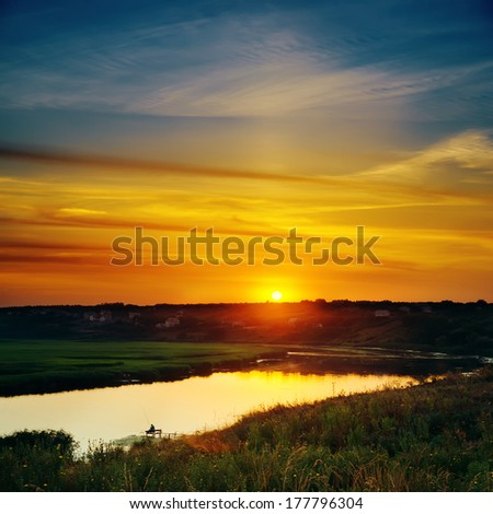 last sunrays in sky over river - stock photo