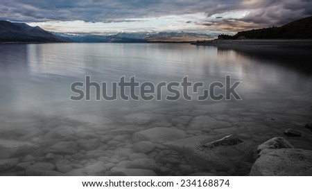 Last sunrays touching the surface at Lake Pukaki, New Zealand - stock photo