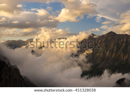 Last warm sunlight on alpine valley with glowing mountain peaks and scenic clouds. Italian French Alps, summer travel destination. - stock photo