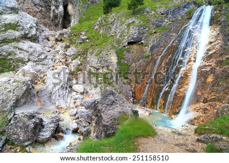 Lasties valley with blue pond and small waterfall surrounded by large boulders, Sella massif, Dolomite Alps, Italy - stock photo
