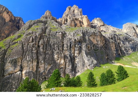 Lasties Valley with green trees and grass beneath tall walls of Sella massif, Dolomite Alps, Italy