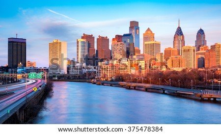 Late afternoon in Philadelphia.  The skyline glows under an orange sunset light. Schuylkill expressway traffic runs parallel to Schuylkill river. - stock photo