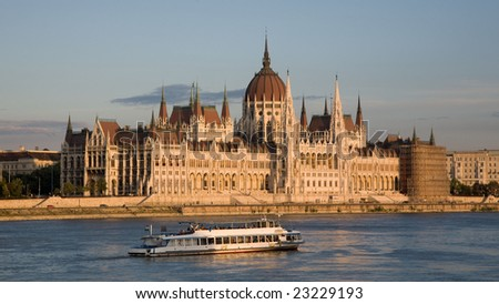 Late afternoon shot of the Parliament of Hungary in Budapest on the bank of the Danube River with a boat on the river in the foreground. - stock photo