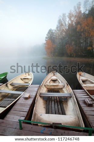 Late autumn foggy morning. Small wooden pier with rowboats on still lake - stock photo