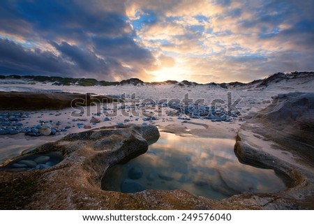 Late evening landscape beach over rocky shore with glowing sunset