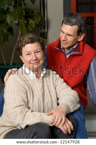 Late middle age, mature, senior couple portrait on front porch. Man gazing lovingly at woman