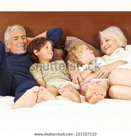 Late senior parents laying with two children on bed - stock photo