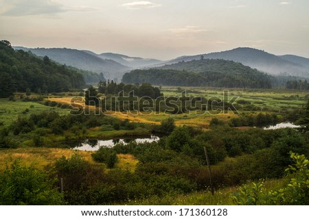 Late summer in the Adirondack Mountains in New York with a swampy foreground and fog in the background mountains. - stock photo