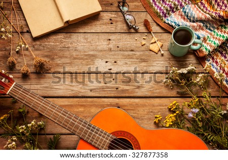 Late summer or autumn relaxation, rustic background on wood from above. Country lifestyle, rural vacation or agrotourism concept. Layout with free text space. Book, blanket, coffee and guitar. - stock photo