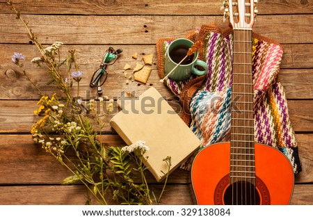 Late summer or autumn relaxation, rustic background on wood from above. Country lifestyle, rural vacation or agrotourism concept. Book, blanket, coffee and classic guitar. - stock photo