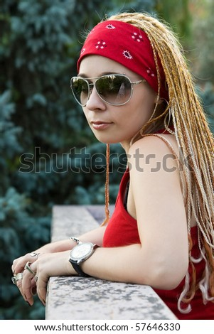 Late teenage girl with braids posing outdoors - stock photo