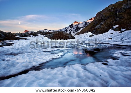 late winter scenery of icy alpine lake with sunrise reflections