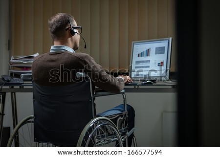 Late working man on wheelchair giving support assistant - stock photo