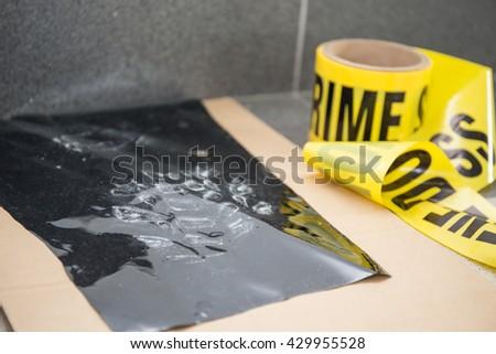 latent footprint evidence with crime scene tape in crime scene investigation - stock photo